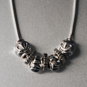 photo of silver chain with heart, cog and flower beads