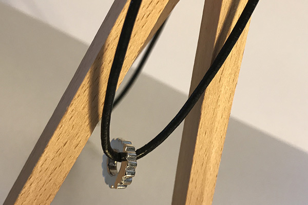 photo of a leather necklet with a silver wheel bead