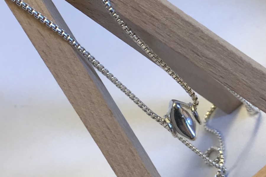photo of a silver box chain hanging on a stand