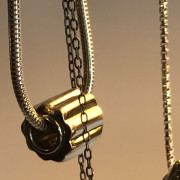 close up photo of a silver bead on a silver snake chain