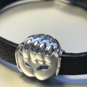 close up photo of a silver hand bead on a leather wrist strap